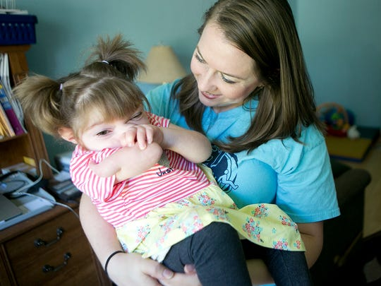 Natasha Thompson holds her daughter Violet, 3, at her home in Stevens Point, Friday, Sept. 4, 2015. Violet was one of 12 children in the world born with a chromosomal deletion.