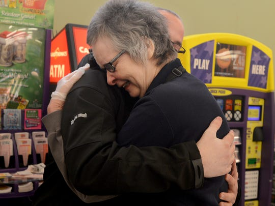 Cathy Barker hugs her son, Jason, after winning the Covering the Community roof giveaway from Reed's Metals, Inc., Friday morning.