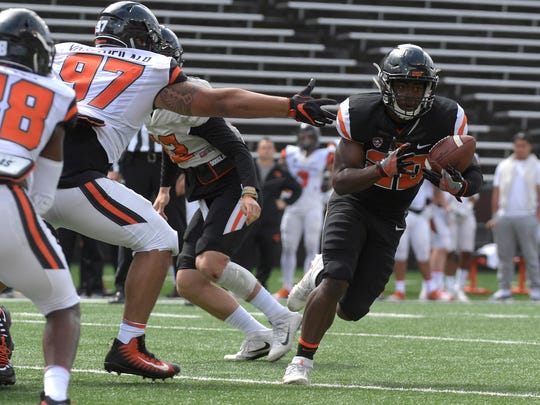 Oregon State's running back B.J. Baylor avoids defensive tackle Kalani Vakameilalo while rushing for a touchdown in an NCAA college football spring scrimmage Saturday, April 28, 2018, in Corvallis, Ore. (Mark Ylen/Albany Democrat-Herald via AP)