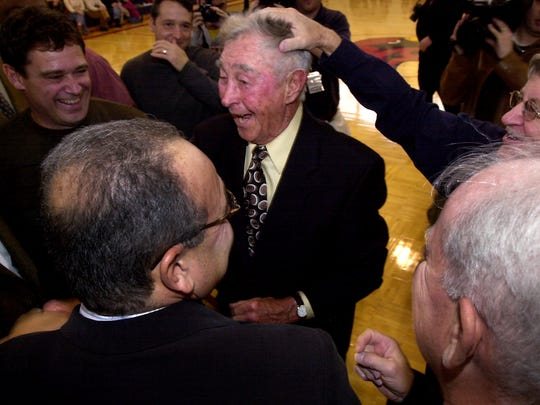 Bobby Wanzer, the first basketball coach at St John Fisher, is celebrated by basketball alumni at the dedication of the court in his name at Fisher. James Leary, far right, (class of '68) gives him a pat on the head Feb. 21, 2006.