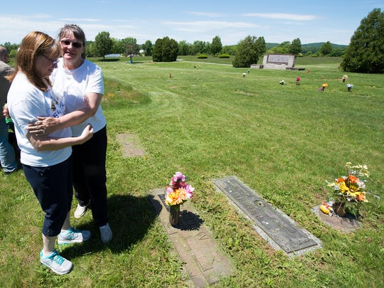 Jennie Heiner, right, hugs her sister Ida Fleming as they look over the grave of a baby granddaughter after Heiner moved the grass around the memorial at Suburban Memorial Gardens in Conewago Township. The family has six relatives at the cemetery and Heiner has a plot for herself.
