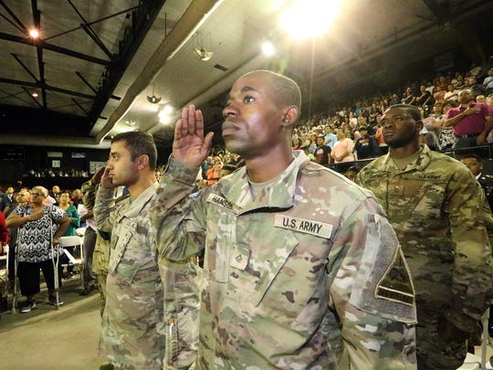 U.S. Army Pvt. 2nd class Andre Hanson, originally from Jamaica, salutes during the national anthem while being among 975 applicants who took the Oath of Citizenship in a ceremony in July inside the El Paso County Coliseum. A group of about 10 military service members became citizens.