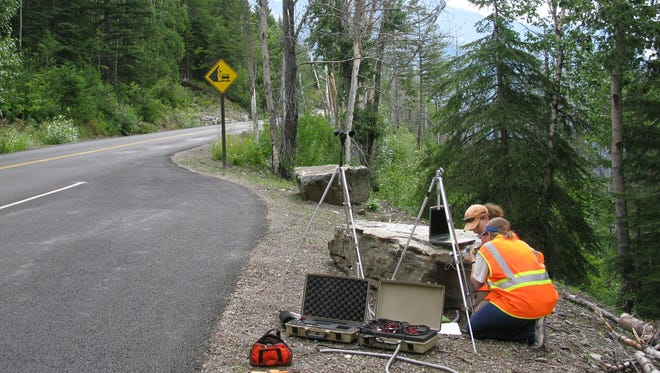 In this photo provided by the National Park Service a National Park Service staffer sets up an acoustic recording station on Going-to-the-Sun Road to capture the impact of traffic on acoustic conditions in Glacier National Park, Mont.