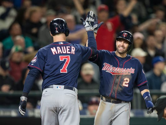Minnesota Twins' Brian Dozier, right, congratulates Joe Mauer after Mauer hit a two-run home run that scored Dozier during the fifth inning of a baseball game against the Seattle Mariners on Saturday, May 28, 2016, in Seattle. (AP Photo/Stephen Brashear)