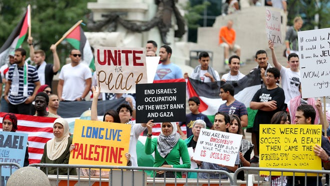 People hoist pro-Palestinian signs and flags during Saturday's rally at Monument Circle.