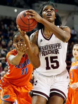 Mississippi State center Teaira McCowan (15) tries to shoot as Florida guard Dyandria Anderson (11) reaches in.