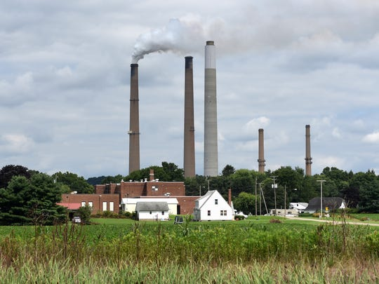 The stacks of the AEP Conesville plant loom over the village in this Tribune file photo. The plant ceased energy production on Wednesday after 62 years of operation. A small staff remains on site for shutdown procedures with official decommission of the facility still set for May 31.