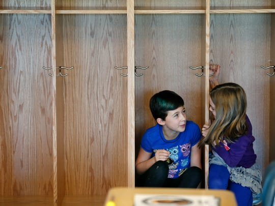 Gwen Giardina, 9, and Anna Brennan, 8, try to fit into the coat lockers while taking a tour of the newly renovated Vollmer Elementary School.