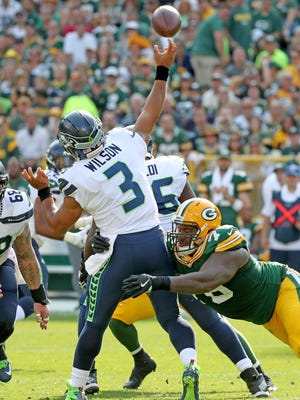 Mike Daniels (76) hits quarterback Russell Wilson (3) as he throws in the second quarter against the Seattle Seahawks Sunday, September 10, 2017 at Lambeau Field in Green Bay, Wis.