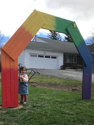 Oaklyn Hardy, 2, stands under the 7-foot rainbow her family built on their property in Middletown.