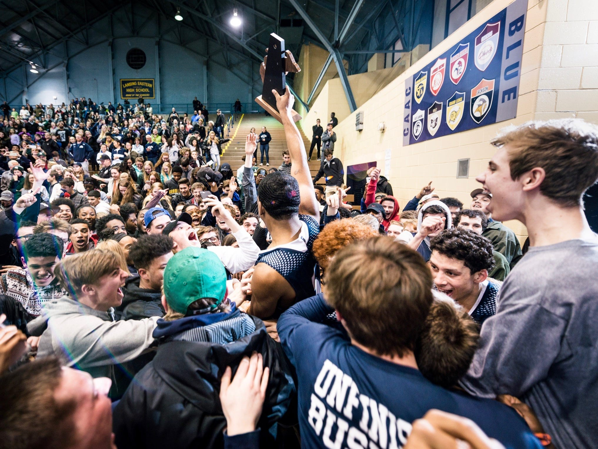 Malik Jones ,center, of East Lansing holds the Class A District Championship trophy as he celebrates with the East Lansing student section after their win over Everett Friday March 10, 2017 at Don Johnson Fieldhouse in Lansing.