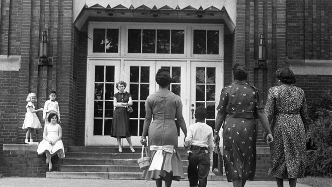 Errol Groves, center, holds the hand of his mother, Iridell Groves, as they walk to Buena Vista School on first day of desegregated in Nashville's schools. Sept. 9, 1957.