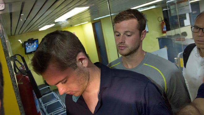 American Olympic swimmers Gunnar Bentz, left, and Jack Conger, right, leave the police station at Rio de Janeiro–Galeão International Airport.