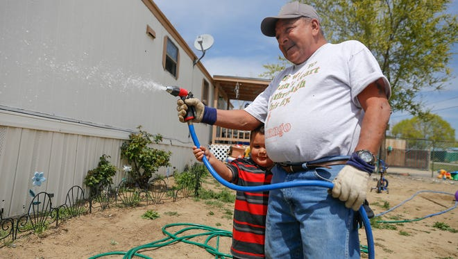 Lloyd Alcon and his grandson Fabian Garcia work in their yard on Monday in the Harvest Gold Subdivsion. A bill signed into law by Gov. Susana Martinez will help the subdivision receive clean drinking water.