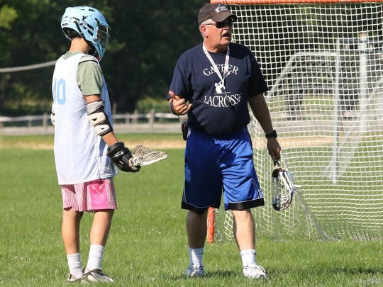 Bob Streeten instructs players during an Elite Gaffer Lacrosse practice at Henry Minier Athletic Field in Big Flats in July.