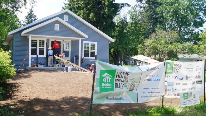 Final touches are put on a home that was built in the Town of Menasha this week in five days as part of a Habitat National Home Builders Blitz.