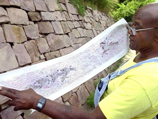 -  -Stoneworker Porter Williams looks over an artist's rendering of a mosaic to be built into the quartzite wall (at rear) along Indian Mound Drive in Sherman Park. The mosaic depicts an American Indian on horseback chasing down a group of buffalo.