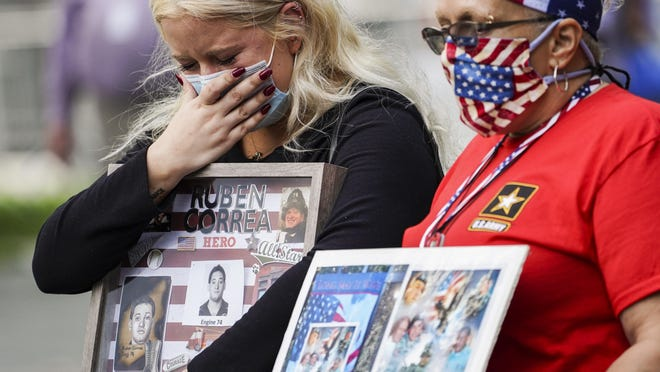 Jo Anne Barbara cries while holding a frame collage of Ruben Correa, a fallen FDNY firefighter, at the National September 11 Memorial and Museum, Friday, Sept. 11, 2020, in New York. Americans will commemorate 9/11 with tributes that have been altered by coronavirus precautions and woven into the presidential campaign.