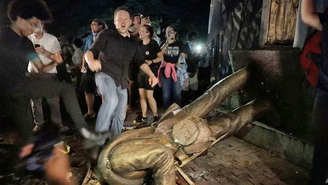 "Protesters celebrate after the Confederate statue known as ""Silent Sam"" was toppled on the campus of the University of North Carolina in Chapel Hill, N.C. late Aug. 20, 2018."