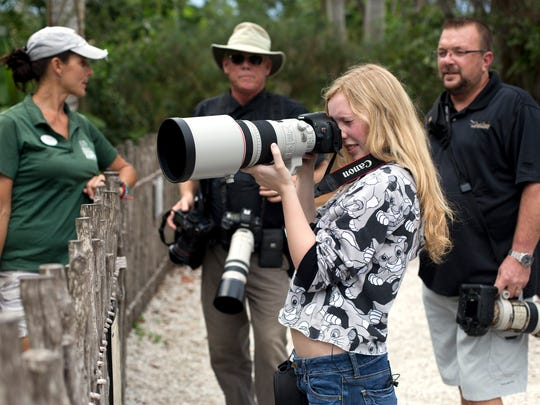 Allison Totterdale, 15, tests out her new 300 mm f/2.8 Canon lens as zoo photographer Larry Richardson, center, and local photographer Dennis Goodman, right, watch at Naples Zoo at Caribbean Gardens on Aug. 27, 2015. Allison, who has Cystic fibrosis, received the lens through Make-A-Wish Southern Florida.