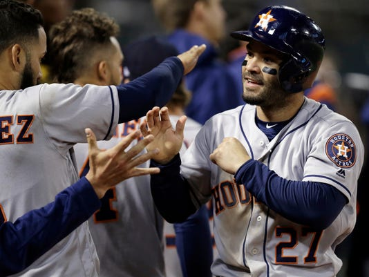 Houston Astros Jose Altuve, right, is congratulated after scoring against the Oakland Athletics during the seventh inning of a baseball game Friday, April 14, 2017, in Oakland, Calif. (AP Photo/Ben Margot)