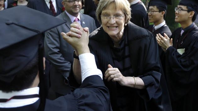 """In this May 30, 2013 file photo Harvard University President Drew Faust clasps hands with a graduate as she walks in the procession at commencement ceremonies in Cambridge, Mass. President Faust, who was the first woman to lead Harvard University, announced Wednesday, June 14, 2017, that she will leave her post after the upcoming academic year saying in a letter """"it will be the right time for the transition to Harvard's next chapter, led by a new president."""""""