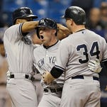 New York Yankees' Slade Heathcott, center, celebrates his three-run home run off Tampa Bay Rays relief pitcher Brad Boxberger with Chris Young, left, and Brian McCann, right, during the ninth inning of a baseball game Monday, Sept. 14, 2015, in St. Petersburg, Fla.