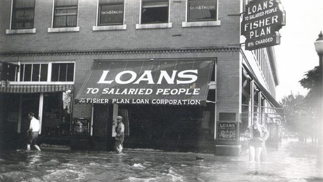 One of many occupants at 28 1st Ave. was Fisher Loan Company, shown during the 1929 flood. Note the woman on the right wearing a bathing costume.