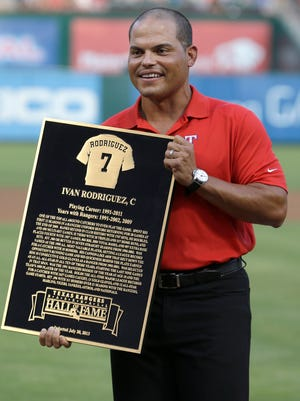 Former Texas catcher and 14-time All-Star Ivan Rodriguez holds his plaque after he was inducted into the Rangers Baseball Hall of Fame in a ceremony before the game against the Orioles in 2013 in Arlington, Texas.