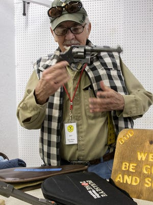 """Gun collector Robert """"Bud"""" Light explains the history of his 1877 Colt """"Thunderer"""" Friday during the San Juan Wildlife Federation Gun and Knife Show at McGee Park."""