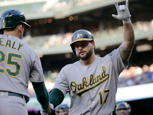 Oakland Athletics' Yonder Alonso is greeted by Ryon Healy after hitting a solo home run o a pitch from Seattle Mariners' Andrew Moore during the third inning of a baseball game, Saturday, July 8, 2017, in Seattle. (AP Photo/John Froschauer)