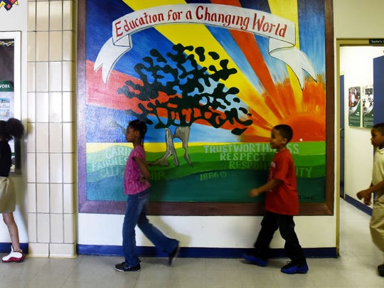 Students walk past a colorful billboard in the hall at Linwood Public Charter School.