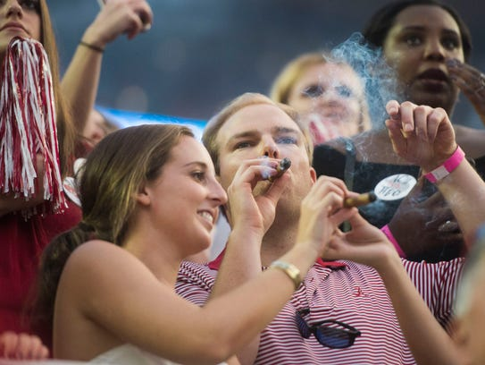 Alabama fans smoke cigars at the end of the Tennessee