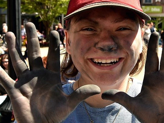 The chalky hands and smile of Raven Chambers, 16, a Fulton High School sophomore, at the 10th annual Dogwood Arts Chalk Walk in Market Square on Saturday, April 21, 2018.