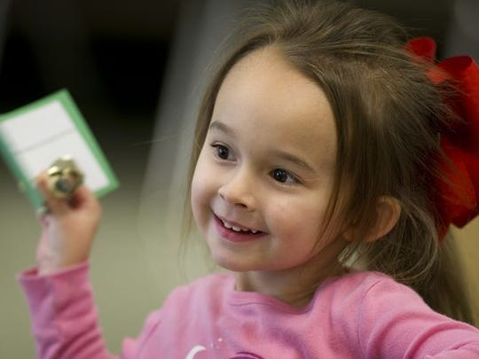 Sophia Overfield, 3, arrives back at her classroom to find a bell and a golden ticket at Holy Name Early Learning Center in this file photo from December 2016.