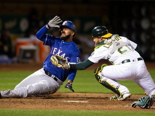 Oakland Athletics catcher Jonathan Lucroy (21) puts the tag on Texas Rangers right fielder Nomar Mazara as he attempts to score on Robinson Chirinos' hit during the sixth inning of a baseball game Tuesday, April 3, 2018, in Oakland, Calif. (AP Photo/D. Ross Cameron)