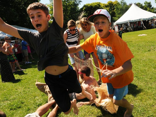 Tina says: Fun at its finest as Tyler Teske, left, and Brandon Stillman, both of Sturgeon Bay, lose their potato sack but leave fallen competitors behind as they leap to the finish line in the old-fashioned games provided during the Fish Creek Summer Festival on July 5.