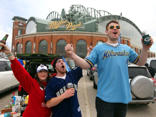 Mike Schwind (right), of Milwaukee yells in excitement while tailgating with friends, Sara Meier (far left) and Ben Beohnlein, also of Milwaukee, while tailgating in the Miller Park lot before the 2014 home opener.