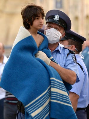 A Maltese policeman carries a child rescued by the Armed forces of Malta at Hay Wharf in Valletta on Saturday. More than 140 survivors, plucked from the sea after their overloaded boat sank in the latest deadly migrant tragedy to hit the Mediterranean. The sinking killed more than 30, most of them women and children, when the boat packed with people desperate to reach European shores went down off Malta near the Italian island of Lampedusa, according to officials.