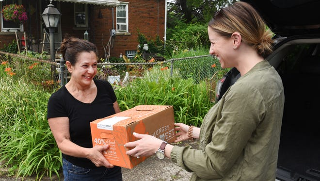 Jess White, right, market manager of Hungry Harvest, delivers a box of produce to subscriber Toby De Simone of Livonia.