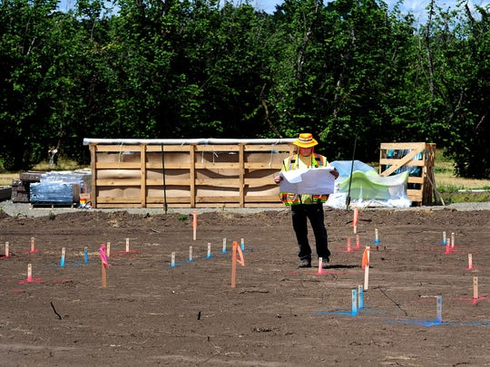 David Louden checks that where posts will be dug correspond with his plan as pre-work begins on the Keizer Big Toy community Build at Keizer Rapids Park, on Thursday, June 4, 2015, in Keizer.