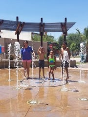 From left to right, Genesis Chacon 11, Bruno Chacon 8, Ariah Baldonado 9, and Noah Perez, 7, play in the water at the Downtown Plaza de Las Cruces splash pad.