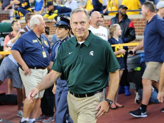 Michigan State coach Mark Dantonio smiles as he enters