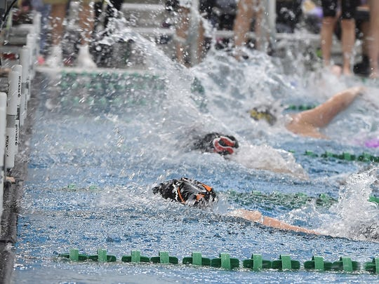 A close finish at the end of the 50-yard freestyle for Molly Banks, center. On bottom is winner Olivia Konzen of Grafton and top is Elaina Falconer of Two Rivers/Manitowoc Roncalli.