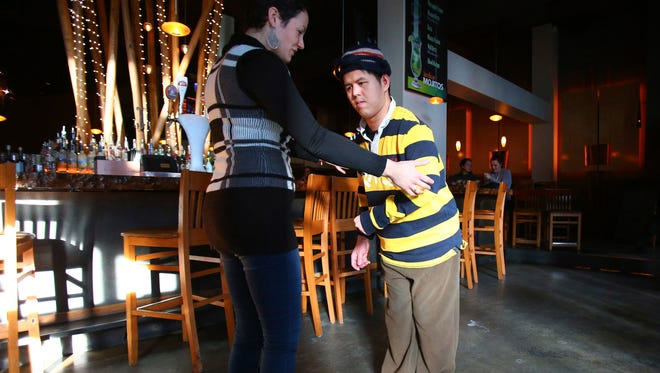 Tango instructor Gabriela Condrea supports Tho Nguyen in March as he walks around the bar before a dance lesson at Amber in Belltown. Nguyen, a stroke victim, didn't walk for years until he came to Condrea's tango lessons.