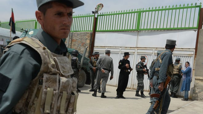 Afghan police stand guard at the gate of the Cure hospital in Kabul on April 24.