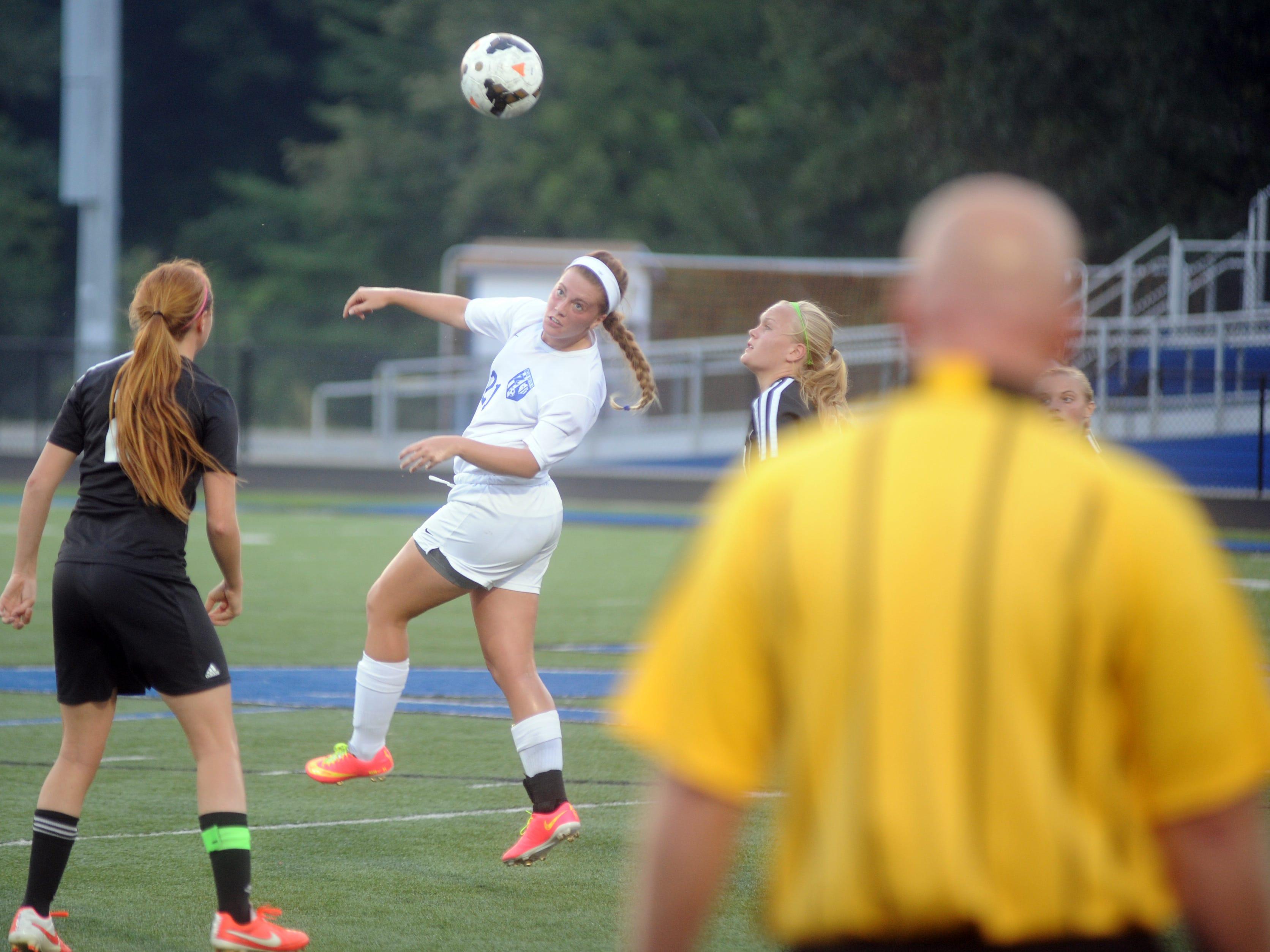 Kylie Mercer of Zanesville heads the ball.