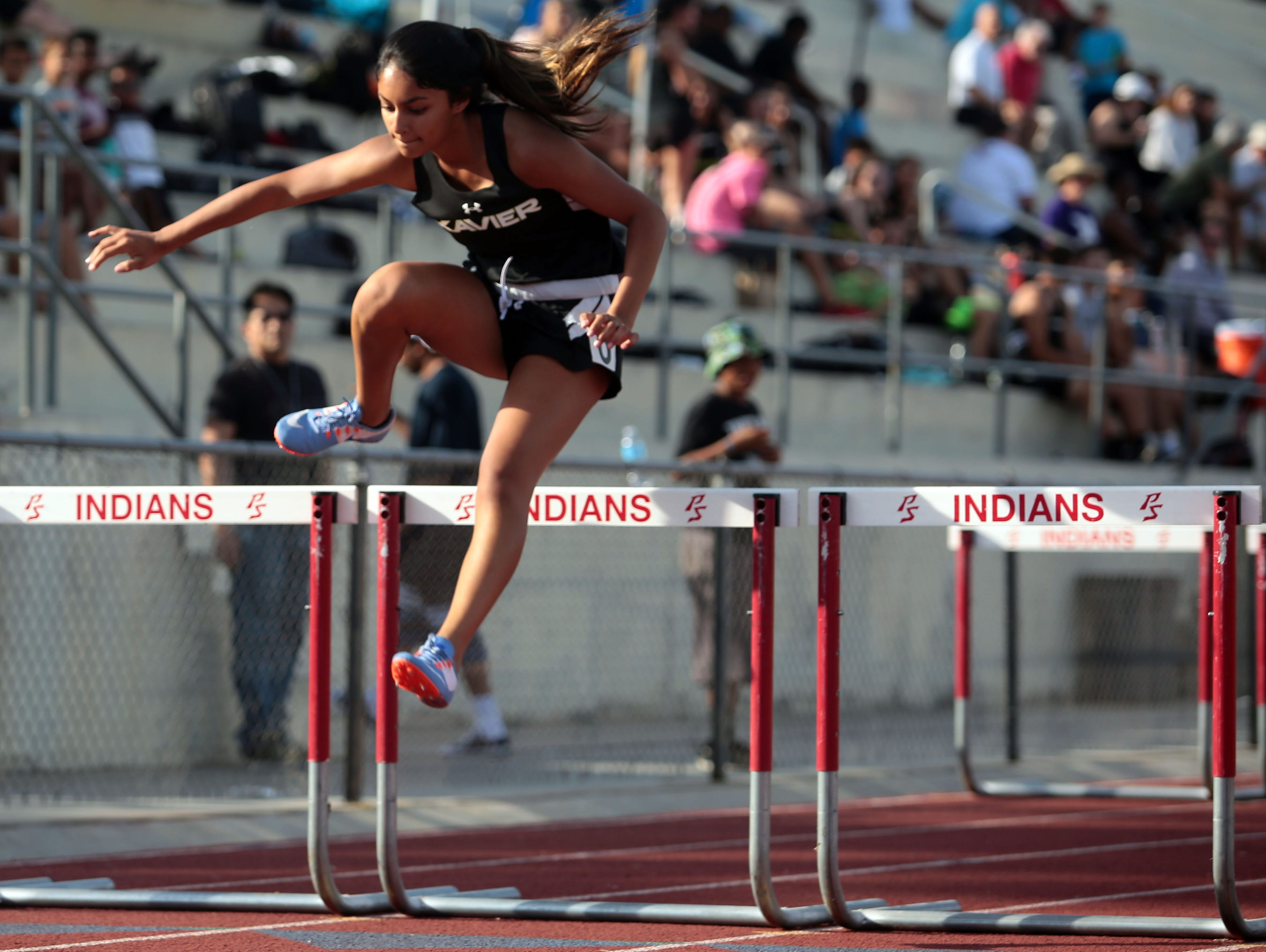 Xavier's Chaya Chandrashekar wins the girls 100m hurdles during a track meet with Palm Springs Thursday, March 16, 2017 in Palm Springs.