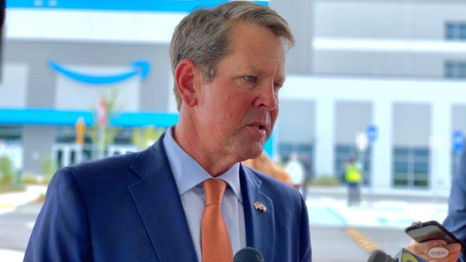 Gov. Brian Kemp speaks with reporters outside Amazon's new warehouse in Gwinnett County on Sept. 1, 2020.