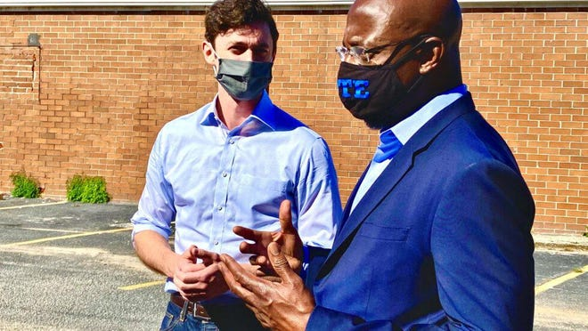 FILE - Rev. Raphael Warnock (right) rallies with Jon Ossoff (left) at a joint campaign stop in DeKalb County in Georgia's U.S. Senate races on Oct. 3, 2020.